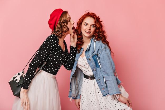 ピンクの背景で話しているカジュアルな服装の巻き毛の女の子。噂を共有する洗練された友人のスタジオショット。