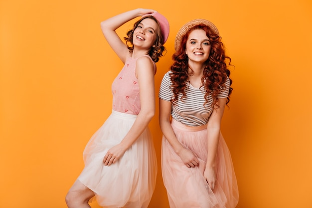 Curly girls in skirts dancing on yellow background. studio shot of gorgeous caucasian ladies expressing happiness.