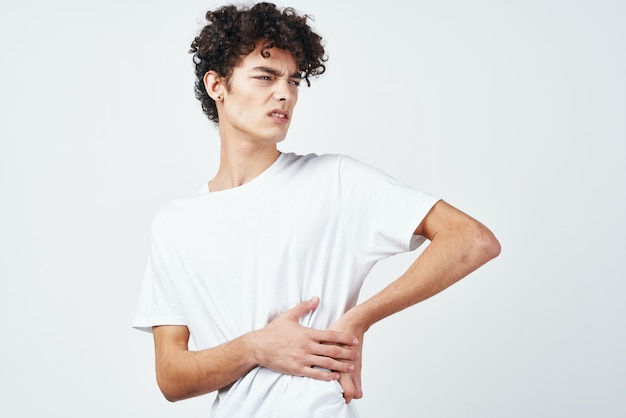 Curly guy in a white tshirt holding his stomach diarrhea discomfort