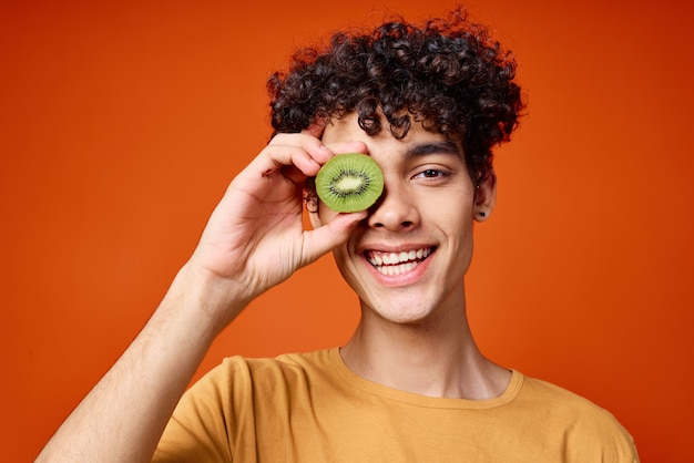 手にキウイを持った巻き毛の男は、新鮮な果物をクローズアップします。高品質の写真