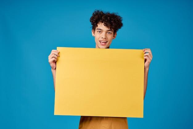 黄色のモックアップポスター青い背景を持つ巻き毛の男