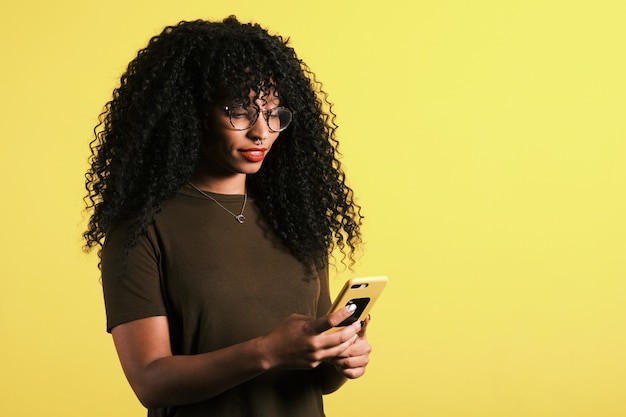 Curly hair afro american woman using her mobile phone