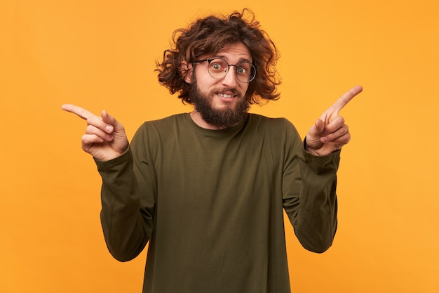 Curly-hair bearded guy in glasses pointing his index fingers at both sides on yellow