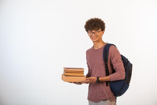 学校の本を保持しているオプティックメガネの巻き毛の少年笑顔と集中しています。
