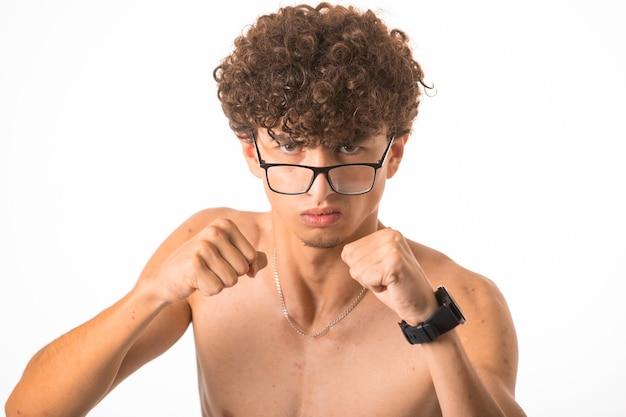 2つの手でパンチングオプティックメガネの巻き毛の少年。