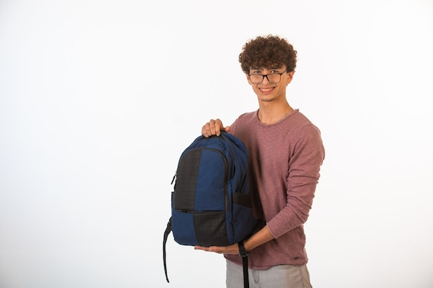 Curly hair boy in optique glasses holding backpack and smiling.
