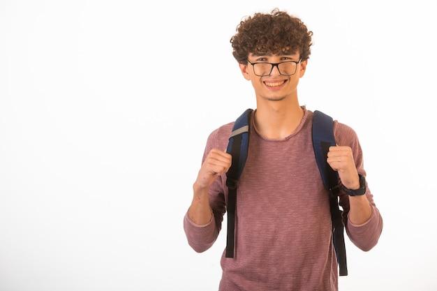 Ragazzo di capelli ricci in occhiali optique che tiene il suo zaino ed è pronto per il viaggio.