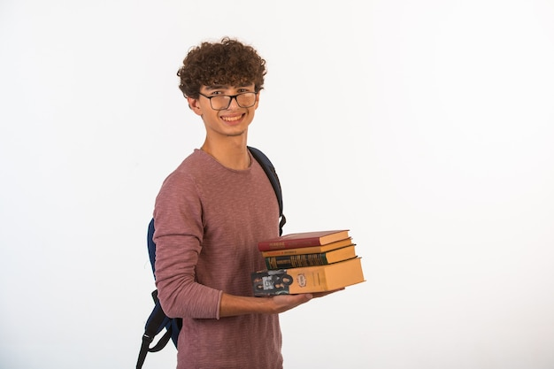 Curly hair boy in optique glasses holding school books and looks motivated