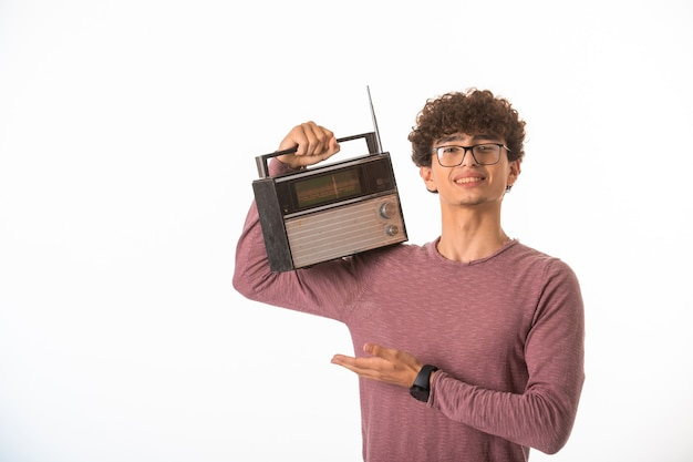 Curly hair boy in optique glasses holding a vintage radio in his shoulders.