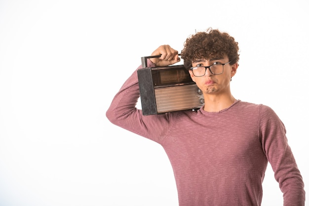 Curly hair boy in optique glasses holding a vintage radio and looks disappointed.
