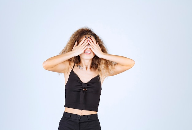 Curly hair girl closing a part of her face with hand.