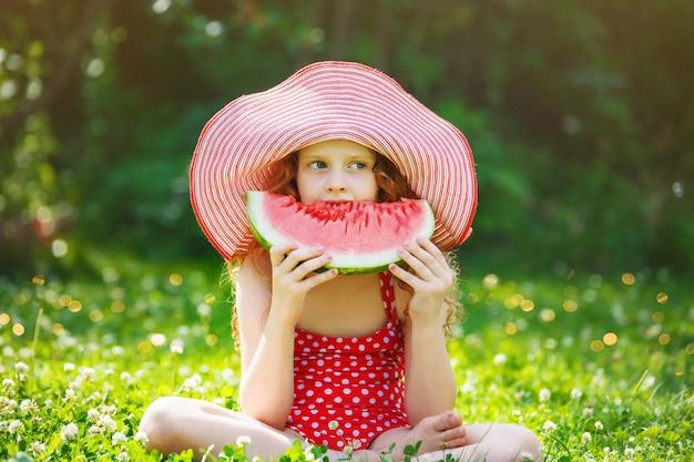 Curly hair girl eating watermelon