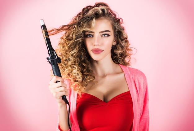 Вьющиеся волосы девушки с парикмахерским оборудованием. профессия индустрии красоты. женщина с длинными вьющимися волосами пользуется щипцами для завивки.