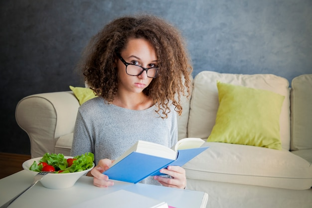 Curly hair teen girl reading book and eating salad