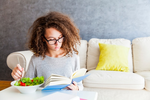 Curly hair teenage girl reading book and eating salad