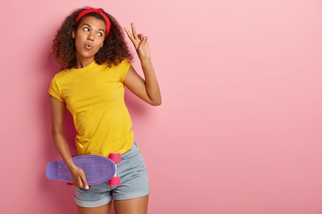 Bella pattinatrice dai capelli ricci in abbigliamento casual, porta lo skateboard, fa un gesto di pace, guarda da parte