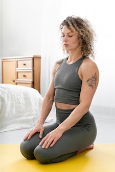 Curly-haired blonde woman doing yoga at home