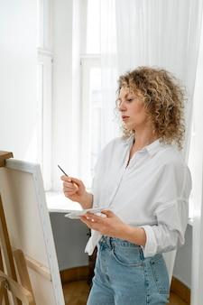 自宅で絵を描く縮れ毛のブロンドの女性