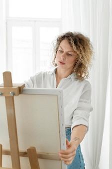 Curly-haired blonde woman painting at home