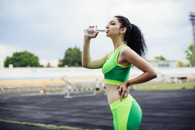 Кудрявая брюнетка занимается спортом на стадионе. девушка пьет воду из бутылки