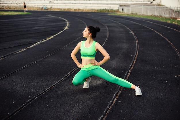 Кудрявая брюнетка занимается спортом на стадионе. девушка делает растяжку, разогрев, упражнения