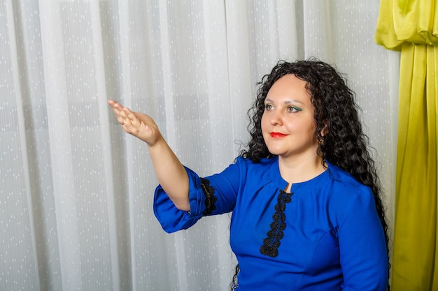 Curly-haired brunette woman in blue points to something with her hand and talks about it. horizontal photo