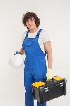 Кудрявый строитель поднимает ящик для инструментов и белый шлем.