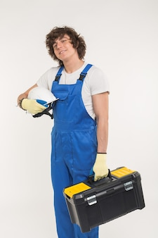 Curly haired builder lifting up toolbox and white