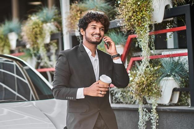 縮れ毛のビジネスマンは笑顔で電話で話します。