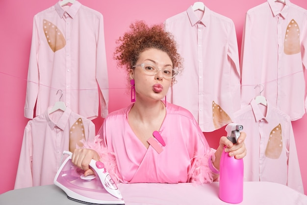 Curly haired busy european woman keeps lips folded busy doing ironing uses water spray wears transparent glasses dressing gown works in laundry has romantic expression. housekeeping concept.