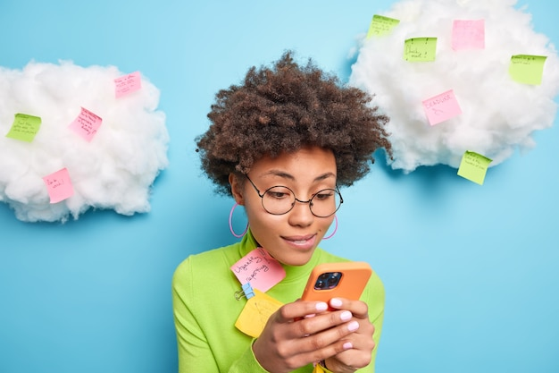 Donna etnica dai capelli ricci concentrata sul display dello smartphone invia messaggi di testo indossa occhiali rotondi girocollo circondato da adesivi con idee scritte e piani