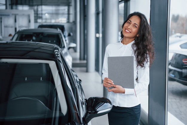 Curly haired female manager stands near the car in automobile salon