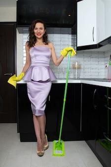 ライラックのイブニングドレスを着た縮れ毛の少女は、緑のモップでキッチンの床を洗います。