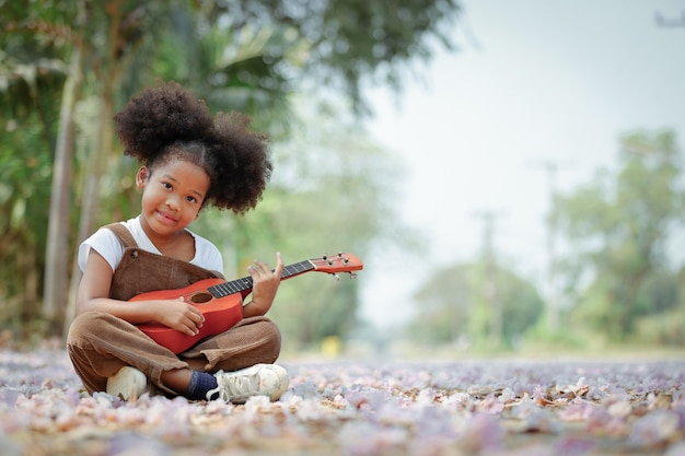 The curly haired girl is enjoying playing the ukulele during the blooming season