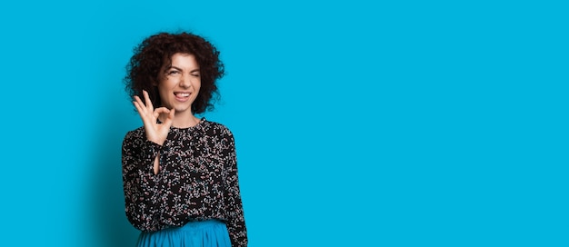 Curly haired  girl is gesturing the okay sign while posing near blue free space