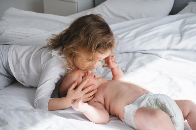 Curly haired girl kissing baby brother on the bed