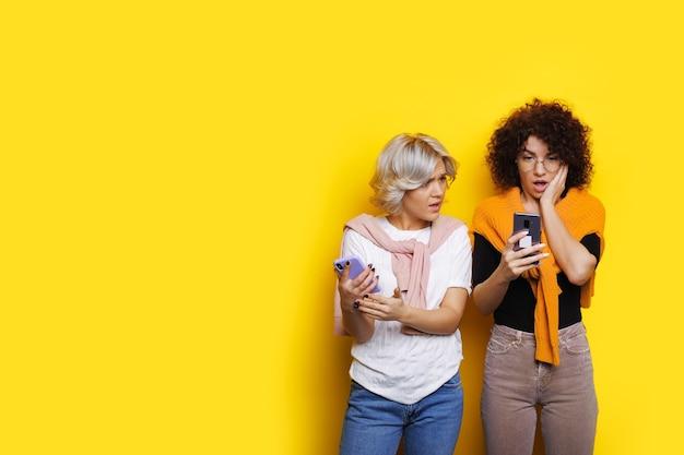 Кудрявая девушка в шоке смотрит на свой мобильный телефон, позируя рядом с подругой на желтой стене