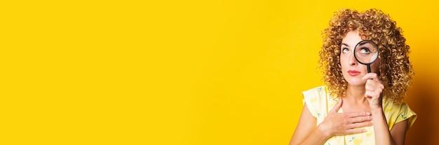 Кудрявая девушка смотрит через лупу на желтую поверхность