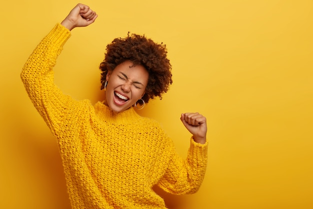 Curly haired girl in winter yellow sweater dances with arms spreading in air, enjoys music, has overjoyed face expression, poses indoor.