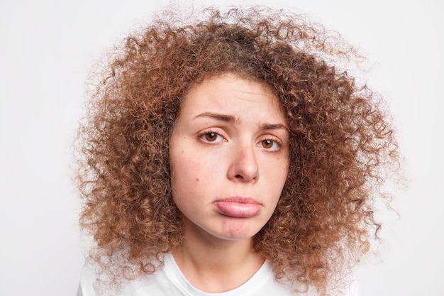 Curly haired grumpy young european woman looks sadly  purses lower lip expresses negative emotions dressed casually isolated over white  wall feels displeased being offended.
