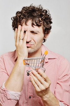 Curly-haired guy with a small trolley for a supermarket in their