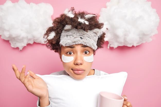 La donna esitante dai capelli ricci si alza all'oscuro alza la palma beve il caffè del mattino ha le piume bloccate nei capelli ricci dopo aver dormito applica cerotti di bellezza per ridurre il gonfiore