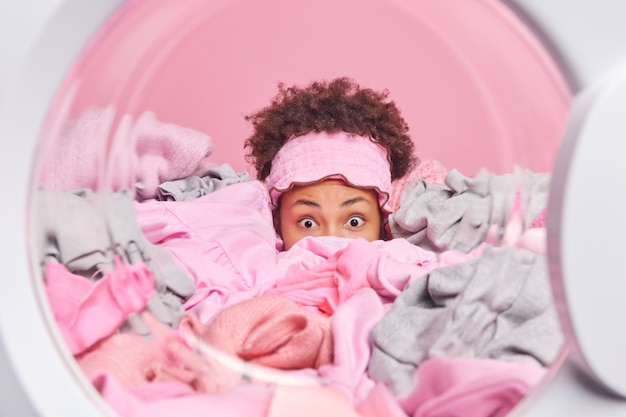 Curly haired housekeeper hidden in stack of laundry poses from inside of washing machine does daily domestic chores poses against pink wall