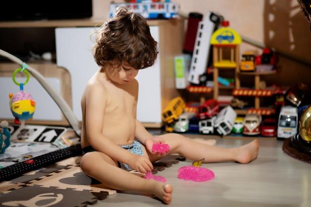 반바지에 곱슬 머리 작은 소년은 옷이 더러워지지 않도록 그의 방에 점액을 가지고 노는.