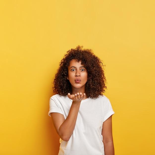 Bella ragazza afro dai capelli ricci manda un bacio d'aria, tiene il palmo vicino alla bocca, vestito con una maglietta bianca, soffia appassionato mwah, tiene le labbra piegate, modelli contro il muro giallo, copia spazio sopra