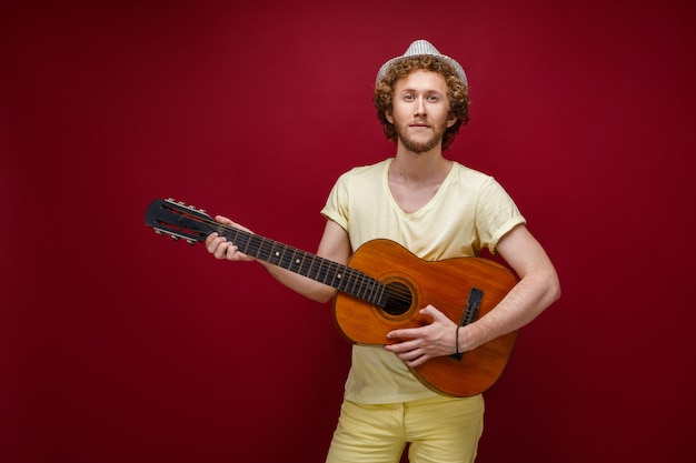 Curly-haired man in hat playing guitar