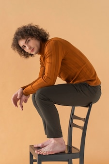 Curly haired man with brown blouse posing on chair