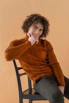 Uomo dai capelli ricci con camicia marrone in posa
