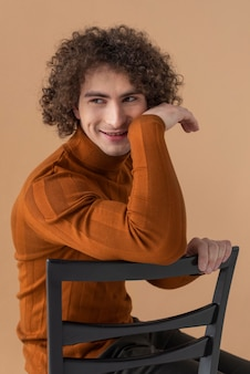 Curly haired man with brown blouse posing