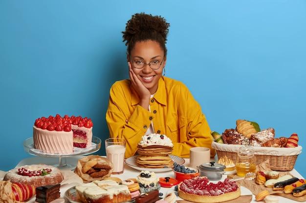Кудрявая симпатичная афро-женщина в очках, окруженная свежими выпеченными кондитерскими изделиями, одетая в желтую рубашку, позирует за столом, собираясь отпраздновать праздничное событие